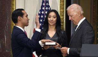 Vice President Joe Biden ceremonially swears in Julian Castro, left, as the new Housing and Urban Development Secretary, Monday, Aug. 18, 2014, in the Eisenhower Executive Office Building on the White House complex in Washington. Castro's wife Erica Castro, holds the bible as his daughter, Carina Castro, center bottom, listens. Castro was officially sworn in on July 28, 2014. (AP Photo/Susan Walsh)