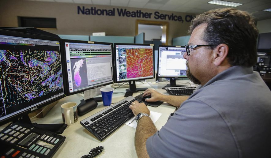In this July 22, 2014 photo, meteorologist Andrew Krein monitors the weather over Lake Michigan while working on the lake marine forecast at the National Weather Service station in Romeoville, Ill. A new system installed in June at the Romeoville office helps the weather service pinpoint storms. (AP Photo/The Herald-News, Lathan Goumas)  MANDATORY CREDIT