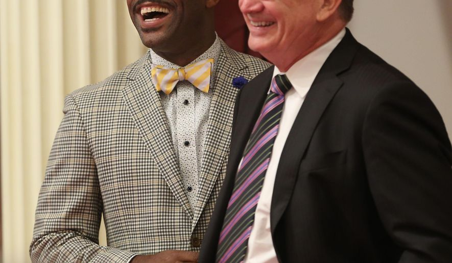 Assemblyman Isadore Hall, Compton, left, and Senate Minority Leader Bob Huff, R-Diamond Bar, smile as Hall's measure prohibiting California state government departments from selling or displaying items with an image of the Confederate flag was approved by the Senate  Monday, Aug. 18, 2014, in Sacramento, Calif.  The bill, AB2444, which excludes non government employees and businesses from the ban, to avoid violating constitutional free speech protections now goes to the governor. (AP Photo/Rich Pedroncelli)