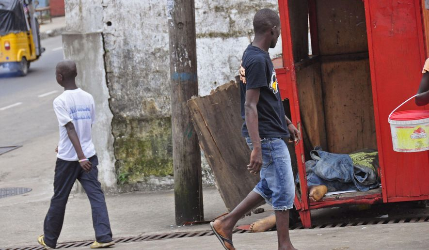 In this photo taken on Saturday, Aug. 16, 2014,  a man, center, looks at the body of another man, right, suspected of dying from the Ebola virus on one of the busiest streets  in Monrovia, Liberia. Liberian officials fear Ebola could soon spread through the capital's largest slum after residents raided a quarantine center for suspected patients and took items including blood-stained sheets and mattresses. The violence in the West Point slum occurred late Saturday and was led by residents angry that patients were brought from other parts of the capital to the holding center, Tolbert Nyenswah, assistant health minister, said Sunday. (AP Photo/Abbas Dulleh)
