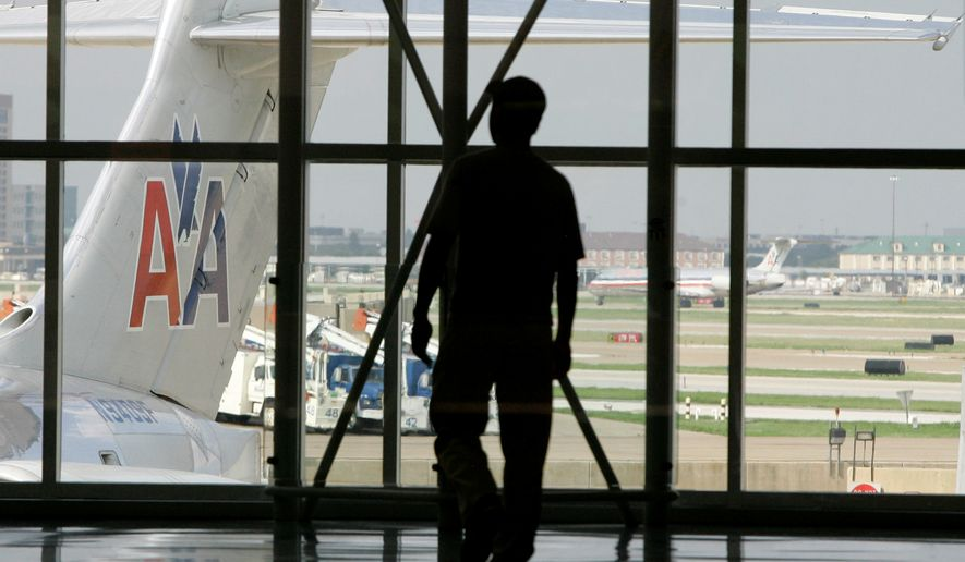 **FILE** The tail of an American Airlines aircraft is seen at left as a person walks by a passenger gate area in Terminal C at Dallas-Fort Worth International Airport in Grapevine, Texas, on Aug. 26, 2008. (Associated Press)