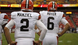 Cleveland Browns quarterback Johnny Manziel stands with quarterback Brian Hoyer before an NFL preseason football game against the Washington Redskins Monday, Aug. 18, 2014, in Landover, Md. (AP Photo/Evan Vucci)