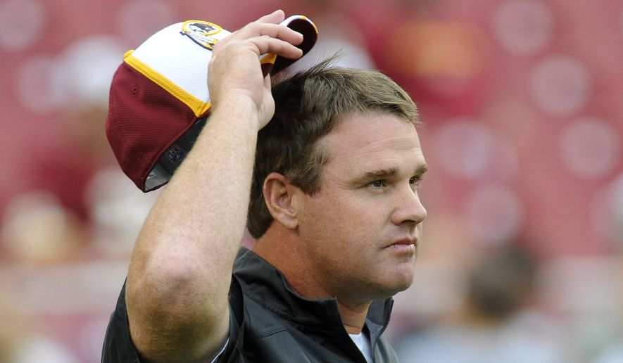 Washington Redskins head coach Jay Gruden pauses on the field before an NFL preseason football game against the Cleveland Browns Monday, Aug. 18, 2014, in Landover, Md. (AP Photo/Richard Lipski)