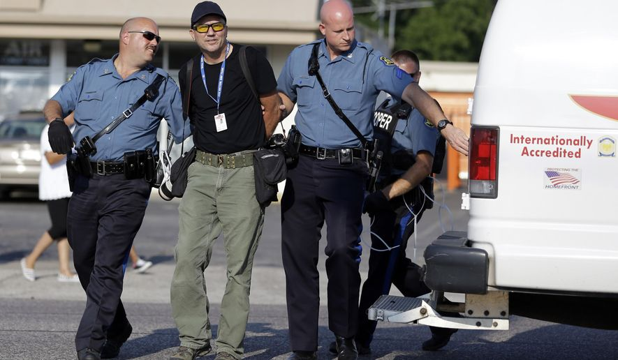 Getty Images photographer Scott Olson is arrested while covering demonstrators Monday, Aug. 18, 2014, in Ferguson, Mo. Missouri Gov. Jay Nixon called in the National Guard Monday after police again used tear gas to quell protesters in the wake of the shooting of Michael Brown. (AP Photo/Jeff Roberson)