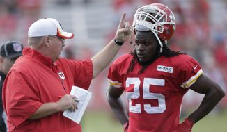 Kansas City Chiefs running back Jamaal Charles (25) listens to coach Andy Reid during NFL football training camp Sunday, July 27, 2014, in St. Joseph, Mo. (AP Photo/Charlie Riedel)