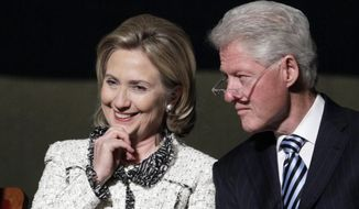 Former U.S. Secretary of State Hillary Rodham Clinton, and former President Bill Clinton, listen to speakers in Washington, Jan. 14, 2011. (Associated Press) ** FILE **
