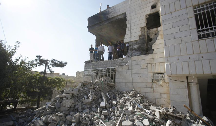 Palestinians stand in what is left of the home of Amer Abu Aisheh, one of three Palestinians identified by Israel as suspects in the killing of three Israeli teenagers, after it was demolished by the Israeli army in the West Bank city of Hebron, Monday, Aug. 18 , 2014. (AP Photo/Nasser Shiyoukhi)
