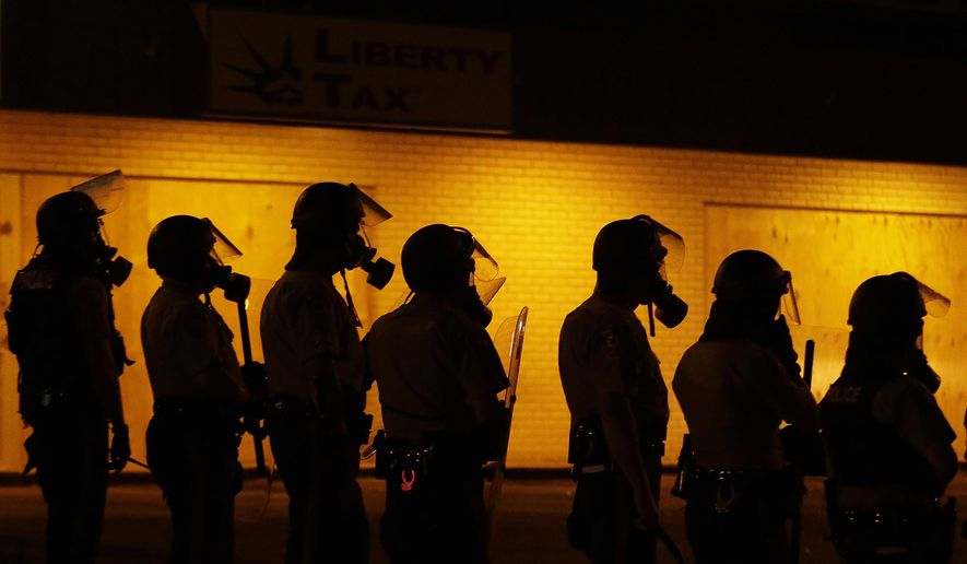 Police wait to advance after tear gas was used to disperse a crowd Sunday, during a protest for Michael Brown, who was killed by a police officer last Saturday in Ferguson, Mo. As night fell Sunday in Ferguson, another peaceful protest quickly deteriorated after marchers pushed toward one end of a street. Police attempted to push them back by firing tear gas and shouting over a bullhorn that the protest was no longer peaceful. (AP Photo/Charlie Riedel)