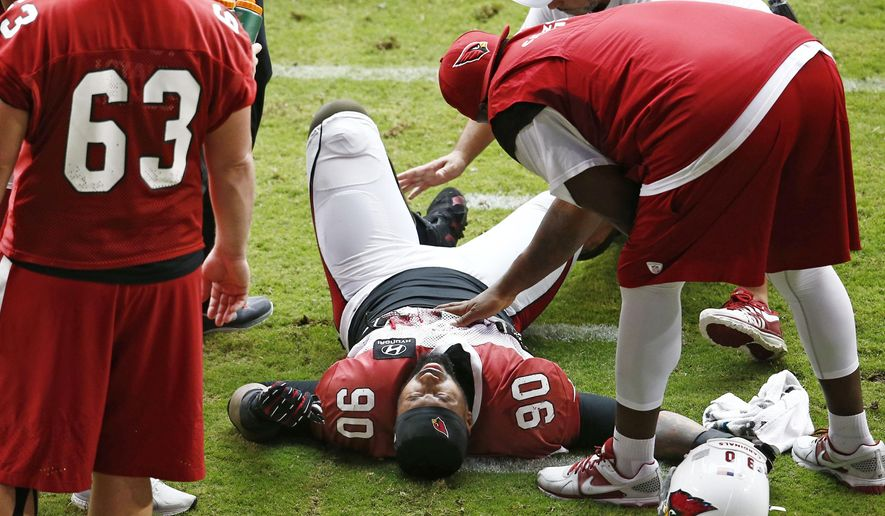 Arizona Cardinals defensive end Darnell Dockett is atended while down in pain during NFL football training camp Monday, Aug. 18, 2014 at University of Phoenix Stadium in Glendale, Ariz. Dockett left the field on a cart. (Photo by Rob Schumacher/The Arizona Republic)  (AP Photo/The Arizona Republic, Rob Schumacher)  MARICOPA COUNTY OUT; MAGS OUT; NO SALES