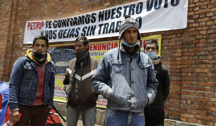 """FILE - In this Aug. 13, 2014, file photo, Colombian bullfighters Omar Rodriguez, left, Alfredo Pena, second left, Diego Torres, second right, and David Rodriguez, right, stand outside La Santa Maria bullring while staging a hunger strike in Bogota, Colombia. Eight bullfighters have been striking for more than a week in tents outside the city's only bullring after Mayor Gustavo Petro ended bullfighting in the city when he cancelled the bullring's lease in June 2012. He said he wanted public places to be used for activities of """"life, not death"""". (AP Photo/Fernando Vergara, File)"""
