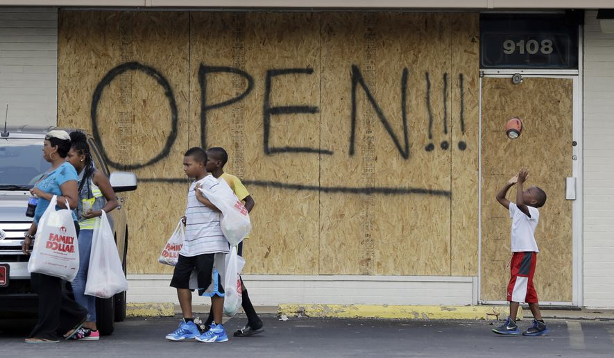 A young boy tosses a football as people walk past a business boarded up to protect against looting Monday, Aug. 18, 2014, in Ferguson, Mo. Missouri Gov. Jay Nixon called in the National Guard Monday after police again used tear gas to quell protesters in the wake of the shooting of Michael Brown. (AP Photo/Jeff Roberson)
