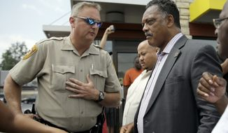 A member of the St. Louis County Police Department asks Rev. Jesse Jackson, right, to move along as they try to keep people from congregating Monday, Aug. 18, 2014, in Ferguson, Mo. (AP Photo/Jeff Roberson)