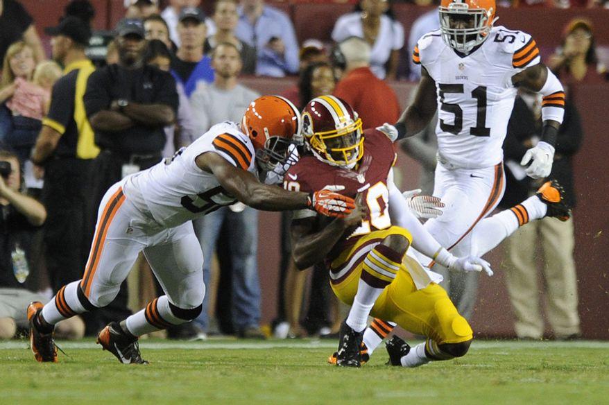 Washington Redskins quarterback Robert Griffin III (10) slides awkwardly after a first quarter run against the Cleveland Browns at FedEx Field, Aug. 18, 2014. (Preston Keres/Special for The Washington Times)