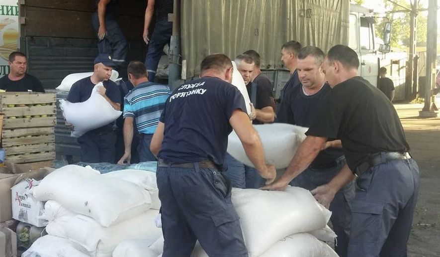 In this image taken Saturday Aug 16, 2014  humanitarian aid is  unloaded at a warehouse in Severodonetsk, Luhansk region, Aug. 16, 2014  to later be distributed to the locals in the conflict zones, and in towns in Luhansk region that have been recently retaken by the Ukrainian army.  After months of rebel occupation and weeks of Ukrainian liberation, the residents of Lysychansk in the Luhansk region a shell-shocked border town say they hope simply to rebuild their former lives _ but fear the return of war to their doorstep.(AP Photo/Vitnija Saldava)