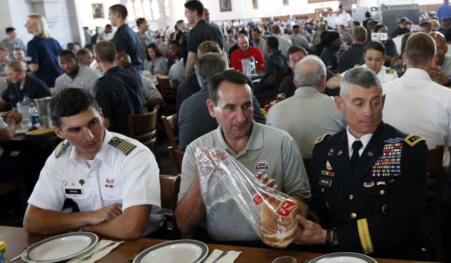 United States men's national basketball team head coach Mike Krzyzewski, center, dines with Lt. Gen. Robert Caslen Jr., superintendent of the U.S. Military Academy, right, at Washington Hall on Monday, Aug. 18, 2014, in West Point, N.Y. The team was at the academy for a practice session. (AP Photo/Mike Groll)