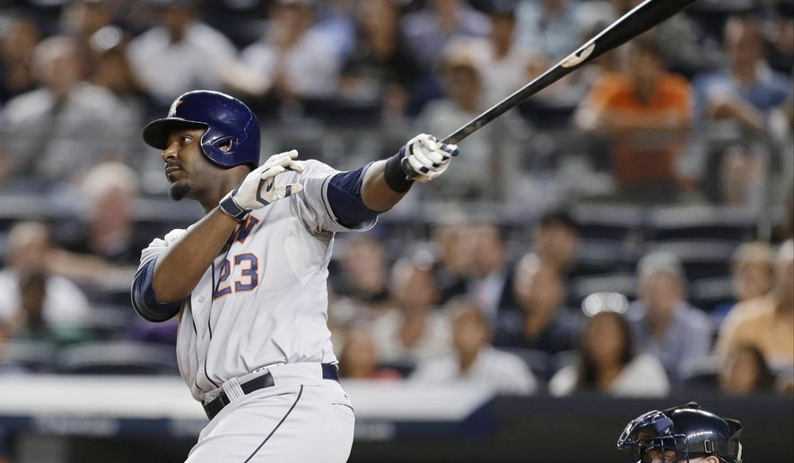 Houston Astros' Chris Carter (23) follows through on a three-run home run during the ninth inning of a baseball game against the New York Yankees on Tuesday, Aug. 19, 2014, in New York. (AP Photo/Frank Franklin II)