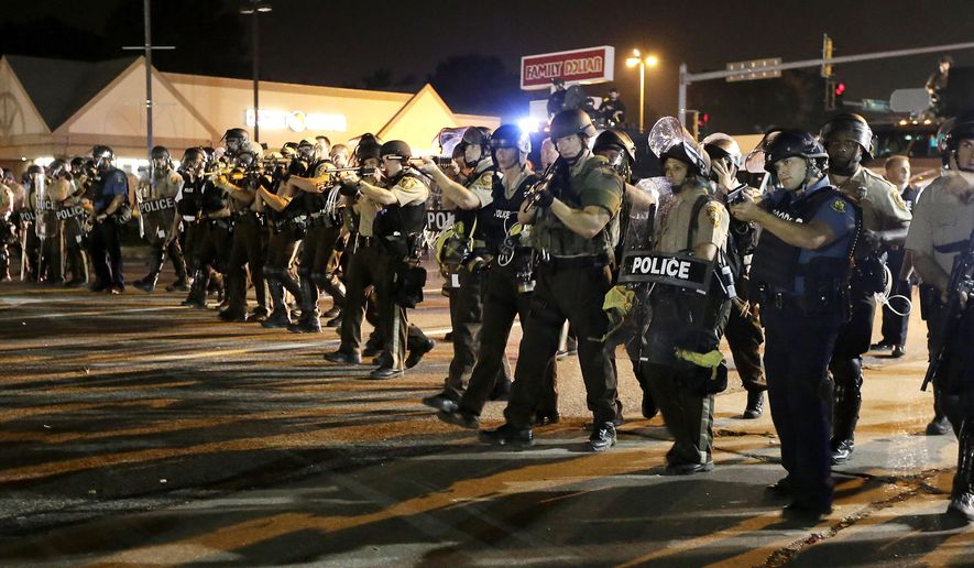 Police advance to clear people Monday, Aug. 18, 2014, during a protest for Michael Brown, who was killed by a police officer Aug. 9 in Ferguson, Mo. Brown's shooting has sparked more than a week of protests, riots and looting in the St. Louis suburb. (AP Photo/Charlie Riedel)