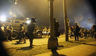 Police scramble in all directions as they take gunfire Monday, Aug. 18, 2014, in Ferguson, Mo. The Aug. 9 shooting of Michael Brown by police has touched off rancorous protests in Ferguson, a St. Louis suburb where police have used riot gear and tear gas and Gov. Jay Nixon ordered the National Guard to help restore order Monday. (AP Photo/Jeff Roberson)