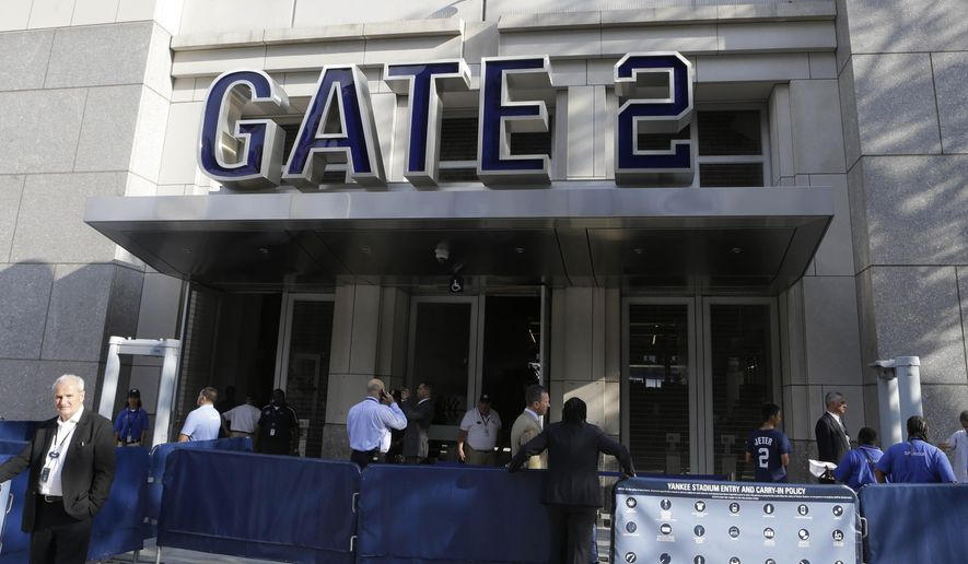 Fans pass through metal detectors as they arrive for a baseball game between the New York Yankees and the Houston Astros Tuesday, Aug. 19, 2014, in New York. (AP Photo/Frank Franklin II)