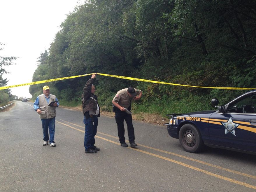 """Investigators leave the scene of a drive-by shooting Tuesday, Aug. 19, 2014 at Bastendorf Beach, Ore. Authorities said a gunman shot five vehicles in a parking lot, killing a Michigan man as he slept, then shot and killed himself. The gunman may also have """"done harm"""" to his father, whose vehicle was found at another rural location in Coos County. The investigation was slowed by the discovery of explosives in the gunman's vehicle. (AP Photo/KCBY, Angelica Carrillo)"""