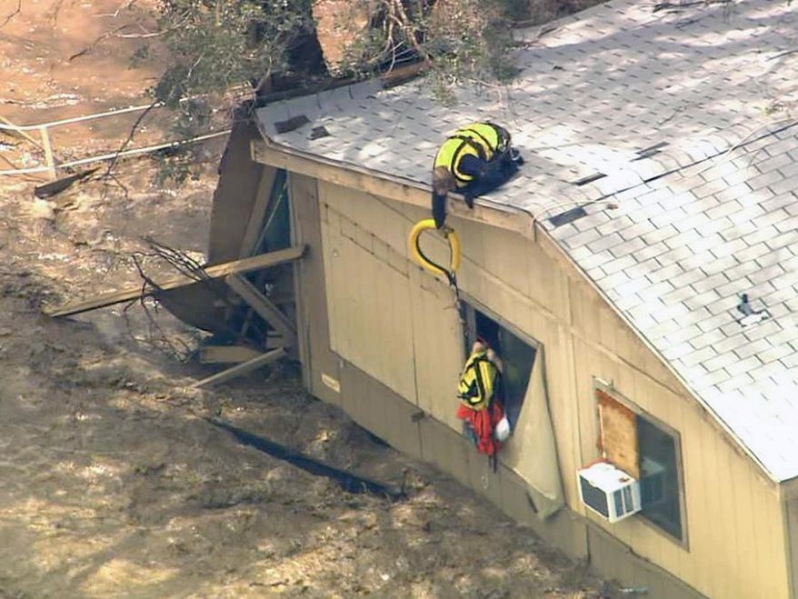 In this image made from a video provided by ABC15 TV, a rescue worker from a helicopter reaches down to residents of a flooded house in New River, Ariz., north of Phoenix, Tuesday, Aug. 19, 2014.  The area was flooded after several inches of rain pummeled the state. (AP Photo/ABC15 TV)