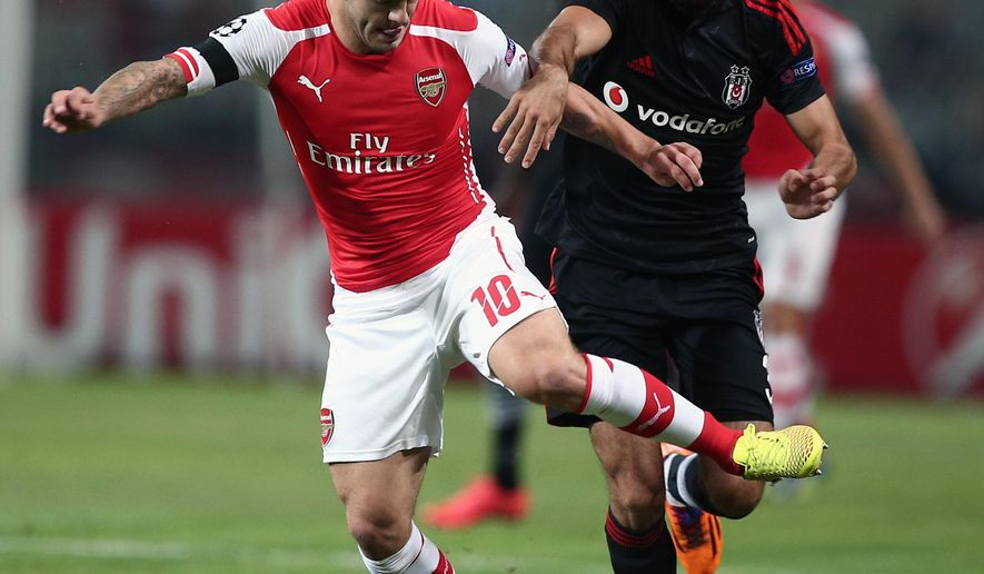 Besiktas's Ismail Koybas, right, and Jack Wilshere of Arsenal controls the ball during their Champions League play-off first leg soccer match in Istanbul, Turkey, Tuesday, Aug. 19, 2014. (AP Photo)