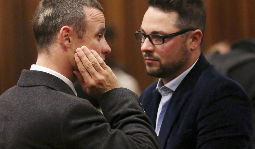 FILE - In this Tuesday May 20, 2014 file photo brother of murder accused, Oscar Pistorius, left, Carl Pistorius, right, speaks with his brother in court in Pretoria, South Africa. Aug. 1, 2014. Carl Pistorius has been discharged from an intensive care unit in the hospital after suffering internal injuries and going into respiratory failure following a car crash Aug. 1, 2014. (AP Photo/Siphiwe Sibeko, Pool, File)