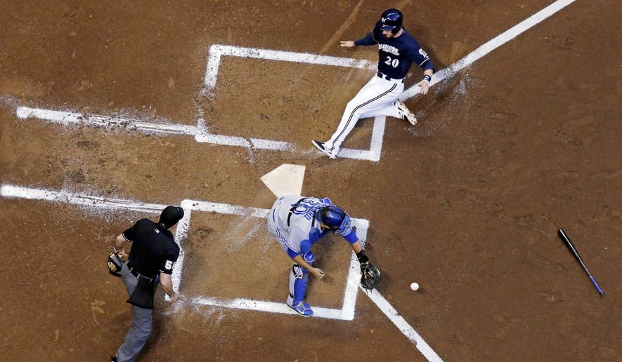 Milwaukee Brewers' Jonathan Lucroy slides safely past Toronto Blue Jays catcher Dioner Navarro, center, during the first inning of a baseball game Tuesday, Aug. 19, 2014, in Milwaukee. Lucroy scored from second on a hit by Aramis Ramirez. (AP Photo/Morry Gash)