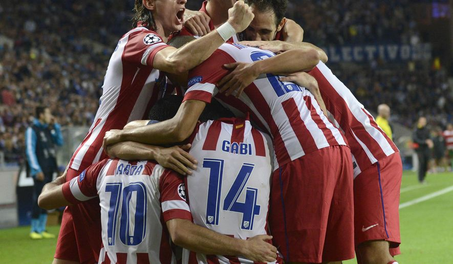 FILE - In this Oct. 1, 2013 file photo, Atletico's Arda Turan, left, celebrates with teammates after scoring his side's second goal during the Champions League group G soccer match against FC Porto, at the Dragao stadium in Porto, northern Portugal. Atletico won 2-1. (AP Photo/Paulo Duarte, File)