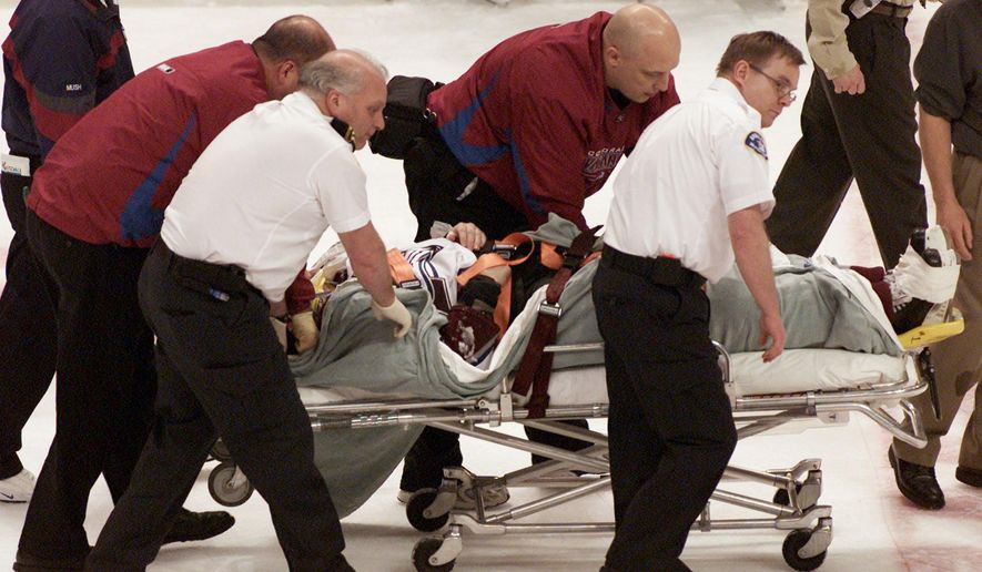 FILE - In this March 8, 2004, file photo, Colorado Avalanche NHL hockey player Steve Moore is taken off the ice by medical staff  after he was hit by Vancouver Canucks'  Todd Bertuzzi during the third period of NHL action in Vancouver, British Columbia. A settlement has been reached in Moore's lawsuit against Bertuzzi for his career-ending hit during an NHL game 10 years ago. (AP Photo/The Canadian Presss, Chuck Stoody, File)