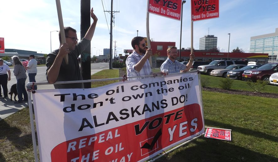 Supporters of an effort to repeal the oil tax cuts approved by the state Legislature in 2013 wave signs along a busy street on primary day, Tuesday, Aug. 19, 2014, in Anchorage, Alaska. (AP Photo/Becky Bohrer)
