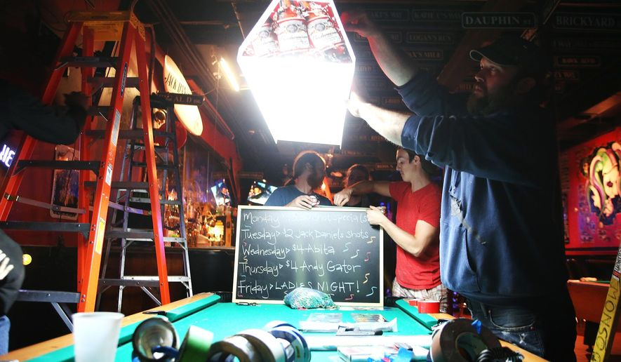 "In this Dec. 18, 2013, photo, Artist Zach DePolo, right, and other crew members stage the Brickyard Bar, for a scene in the movie ""The Prince"" in Mobile, Ala. Because of the Entertainment Industry Incentive Act, companies like Mudbrick Media have shot six feature-length films since it opened in 2008. The state has spent about $22.4 million to bolster the state's film industry. (AP Photo/AL.com, Sharon Steinmann) MAGS OUT"