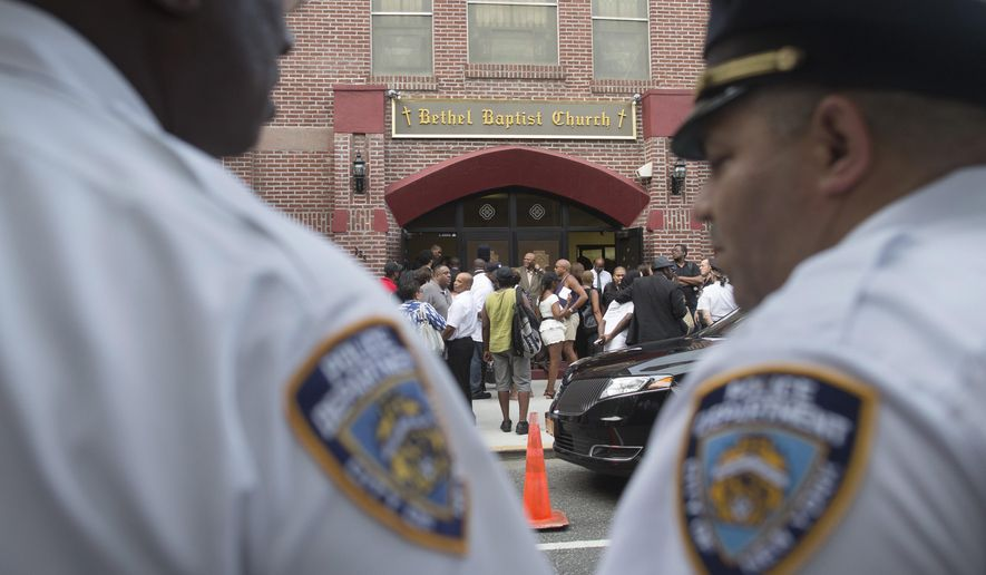 In this July 23, 2014, photo, mourners arrive as ranking NYPD officers stand guard at the funeral service for Eric Garner at Bethel Baptist Church, Wednesday, July 23, 2014, in the Brooklyn borough of New York. (AP Photo/John Minchillo, File)