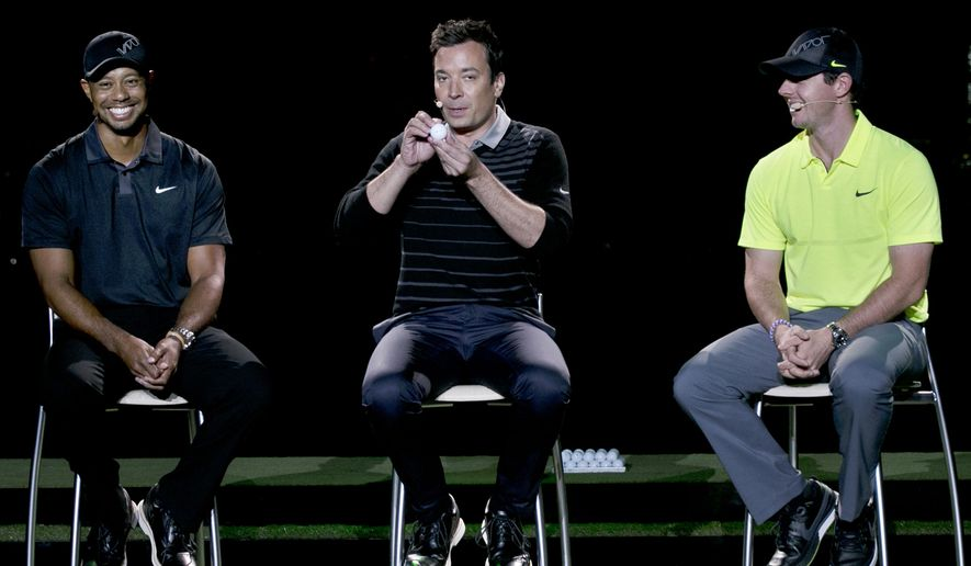 Golfers Tiger Woods, left, and Rory McIlroy right, sit near as television host Jimmy Fallon makes a joke during a golfing demonstration, Monday, Aug. 18, 2014, in Jersey City, N.J.  (AP Photo/Mel Evans)
