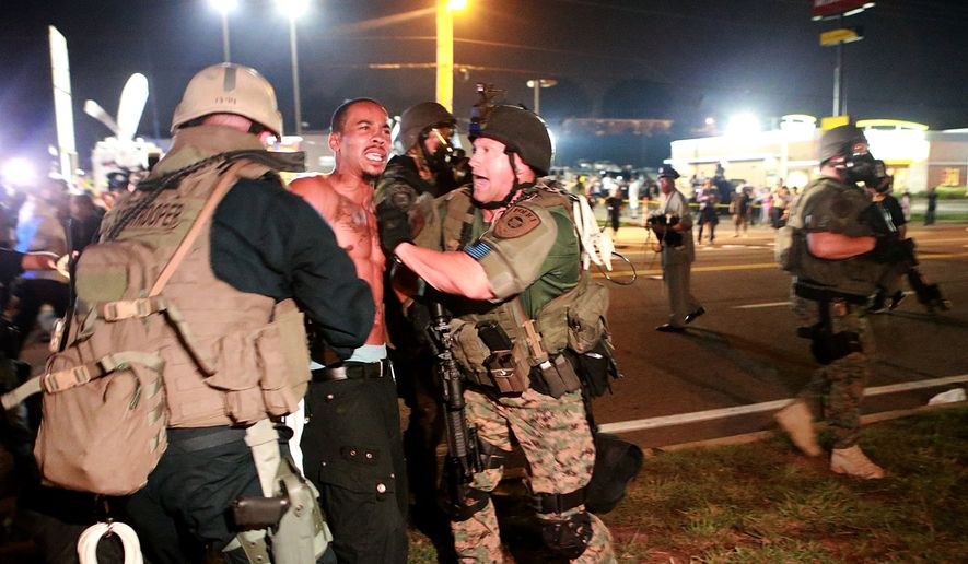 A protestor is detained Monday, Aug. 18, 2014, in Ferguson, Mo. The Aug. 9 shooting of Michael Brown by police has touched off rancorous protests in Ferguson, a St. Louis suburb where police have used riot gear and tear gas. (AP Photo/St. Louis Post-Dispatch, Christian Gooden)