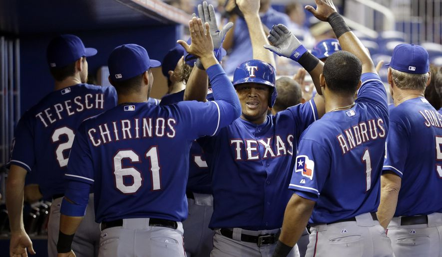 Texas Rangers' Adrian Beltre, center, is congratulated in the dugout after scoring on an error by Miami Marlins shortstop Adeiny Hechavarria in the first inning during an interleague baseball game, Wednesday, Aug. 20, 2014, in Miami. (AP Photo/Lynne Sladky)