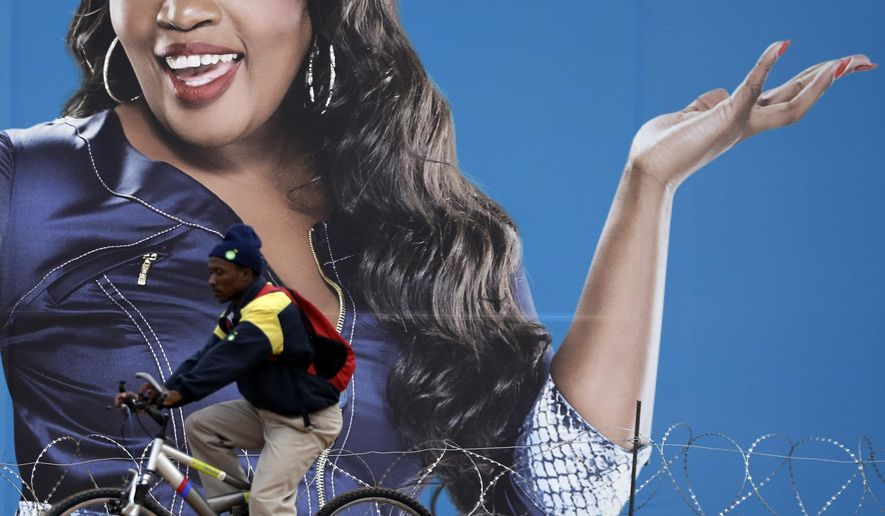 "A man cycles past a billboard featuring Sophie Ndaba, an actor who played the Queen Moroka character in ""Generations,"" soap opera displayed on the street in Soweto, South Africa, Wednesday, Aug. 20, 2014.  ""Generations,"" a hugely popular soap opera in South Africa, first aired in 1993, a year before the nation's first all-race elections ended apartheid. Now the future of this television staple followed by millions is up in the air.(AP Photo/Themba Hadebe)"