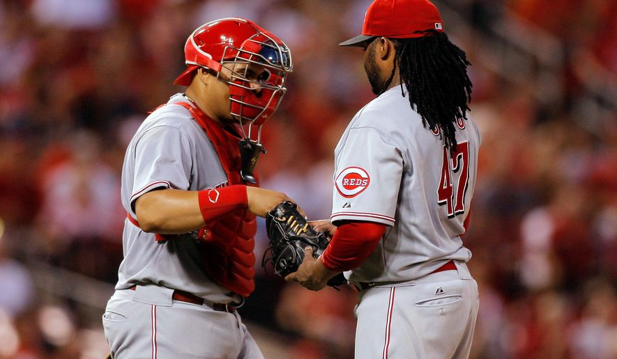 Cincinnati Reds catcher Brayan Pena, left, hands a new ball to starting pitcher Johnny Cueto during the fifth inning of a baseball game against the St. Louis Cardinals on Wednesday, Aug. 20, 2014, in St. Louis. (AP Photo/Scott Kane)