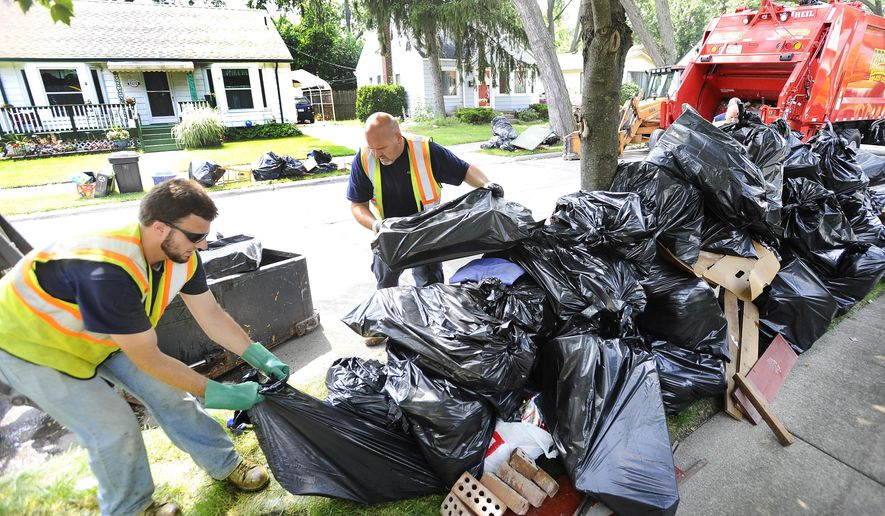 From left, Berkley DPS workers Tom Benaglio and Rod Halas help out Tringali, the Berkley waste and refuge contractor, collect the ever growing piles piles of water-damaged belongings from the curbside of Cambridge in Berkley Tuesday, Aug. 19, 2014.   Trash collectors are overwhelmed by the amount of rain and sewage soaked waste people have removed from their basements in the wake of last week's floods in Metro Detroit.   (Daniel Mears/ The Detroit News)  Detroit News)  (AP Photo/Detroit News, David Mears)  DETROIT FREE PRESS OUT; HUFFINGTON POST OUT