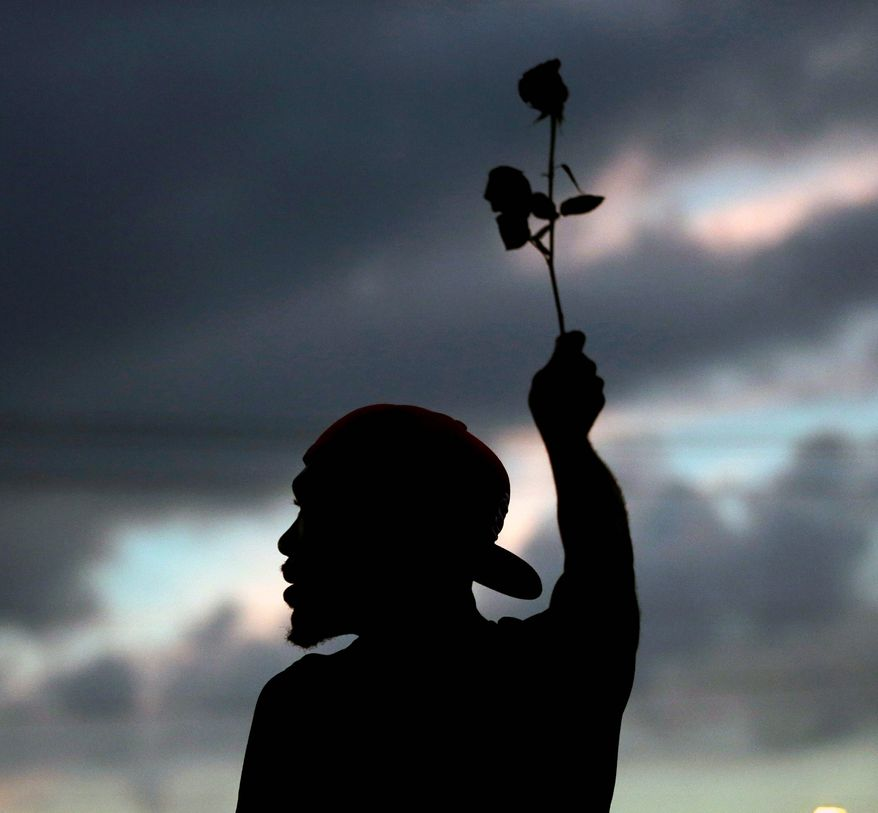 A man holds up a rose during a protest Monday, Aug. 18, 2014, for Michael Brown, who was killed by a police officer Aug. 9 in Ferguson, Mo. Brown's shooting has sparked more than a week of protests, riots and looting in the St. Louis suburb. (AP Photo/Charlie Riedel) A man holds up a rose during a protest Monday, Aug. 18, 2014, for Michael Brown, who was killed by a police officer Aug. 9 in Ferguson, Mo. Brown's shooting has sparked more than a week of protests, riots and looting in the St. Louis suburb. (AP Photo/Charlie Riedel)