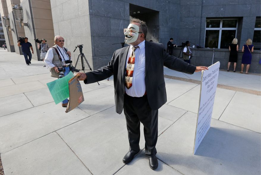 A masked demonstrator hands out literature in front of federal court as part of his protest of the greed of the ex-governor and his wife. (Associated Press)