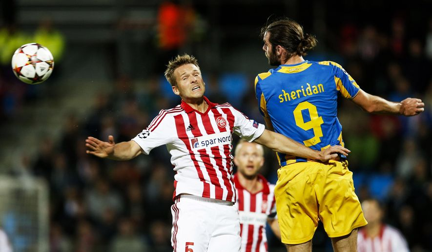 Aalborg BK's Kenneth Emil Petersen, left, and Apoel FC's Cillian Sheridan of Ireland, right, vie for the ball during their Champions League play-off first leg soccer match at Aalborg Stadium, Denmark, Wedensday, Aug. 20, 2014. (AP Photo/Polfoto, Gregers Tycho) DENMARK OUT