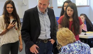 Dan Sullivan, candidate for the Republican nomination for election to the U.S. Senate, signs in to cast his ballot in Alaska's primary election in Anchorage, Tuesday, Aug. 19, 2014. His daughters look on behind him. (AP Photo/Becky Bohrer)