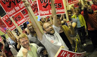 Ballot Measure 1 supporters Nick Moe, left and T.J. Presley lead others in cheers as early returns showed a narrow lead for repealing Senate Bill 21 in downtown Anchorage, Alaska on Tuesday, Aug. 19, 2014. In 2013, Senate Bill 21 narrowly passed the state Senate with the promise that it would attract investment for new wells and put more oil in the trans-Alaska pipeline. Critics called it a giveaway that awarded tax breaks to already profitable oil companies with no guarantee they will invest in Alaska. (AP Photo/Michael Dinneen)