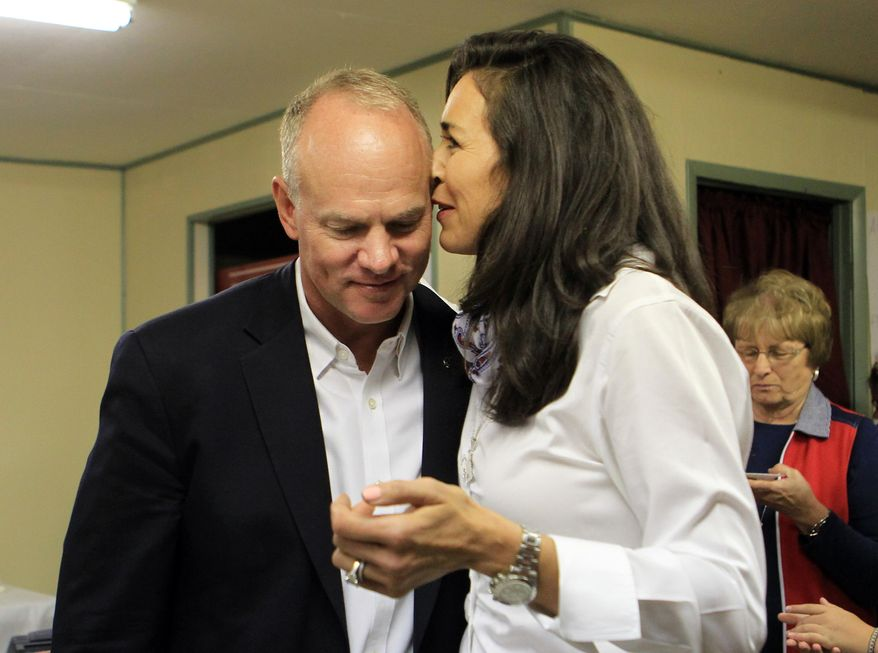 Wyoming Governor Matt Mead listens to his wife, Carol, after winning the primary election over challengers Taylor Haynes and Cindy Hill during a primary election party Tuesday evening, Aug. 19, 2014, in Cheyenne, Wyo.     (AP Photo/The Wyoming Tribune Eagle, Blaine McCartney)