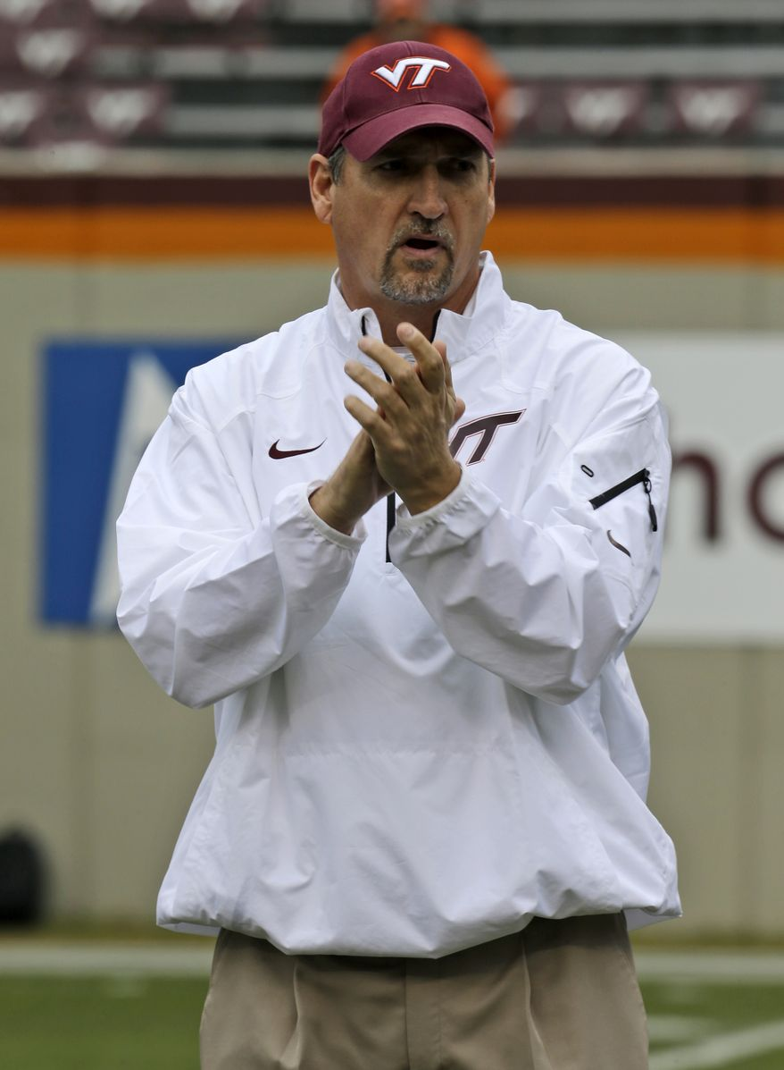 FILE  -  In a Nov. 16, 2013, file photo Virginia Tech defensive coordinator Bud Foster cheers his team prior to the start of the Maryland Virginia Tech NCAA college football game in  Blacksburg, Va. Foster loves it that some are calling Virginia Tech DBU, or Defensive Back U.     (AP Photo/Steve Helber, file)