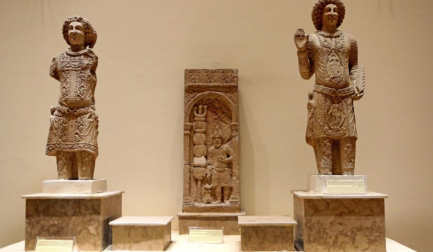 Stone figures depicting the family of Sanatruq are showcased at the Iraqi National Museum in Baghdad, Iraq, Thursday, Aug 21, 2014. Two renovated halls adorned mainly with rare life-size stone statues were inaugurated at the Iraqi National Museum on Thursday geared toward honoring the 5,000 year legacy of the ancient city of Hatra. (AP Photo/Hadi Mizban)