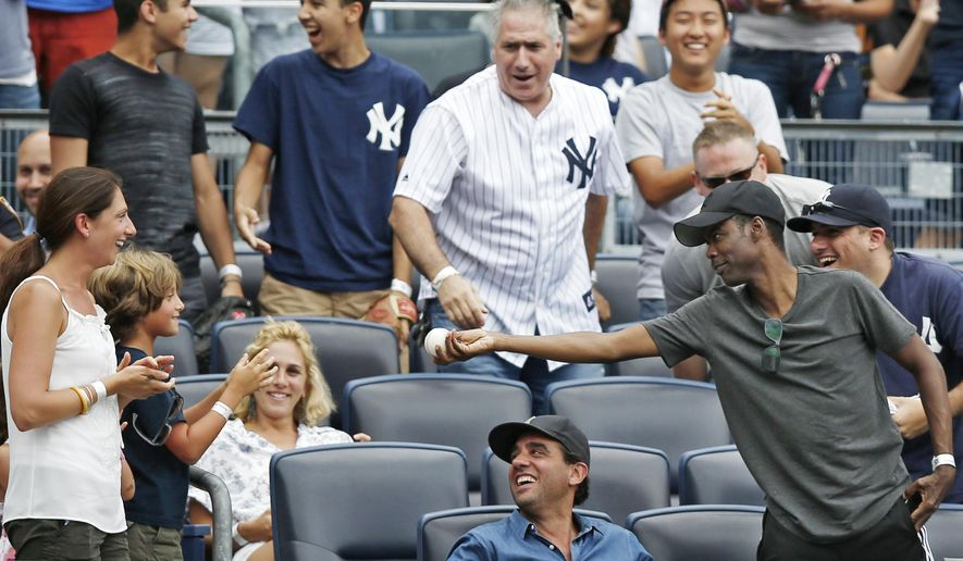 CORRECTS ASTROS BATTER TO JON SINGLETON, NOT MARWIN GONZALEZ - Comedian Chris Rock, far right, offers a foul ball he caught off  Houston Astros' Jon Singleton to a youngster after catching it in the seventh inning of a baseball game against the New York Yankees at Yankee Stadium in New York, Thursday, Aug. 21, 2014.  (AP Photo/Kathy Willens)