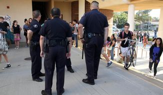 South Pasadena, Calif., police officers greet students as they arrive for the first day of school at South Pasadena High School Thursday, Aug. 21, 2014. Officers were in force Thursday as students began the school year without two peers who allegedly plotted a high school massacre. (AP Photo/Nick Ut )