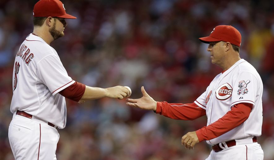 Cincinnati Reds manager Bryan Price, right, takes starting pitcher David Holmberg out in the third inning of a baseball game against the Atlanta Braves, Thursday, Aug. 21, 2014, in Cincinnati. (AP Photo/Al Behrman)